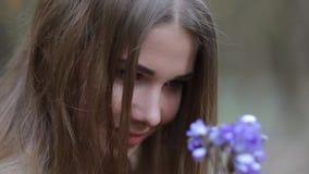 Flickan i parkera som beundrar snödropparna arkivfilmer