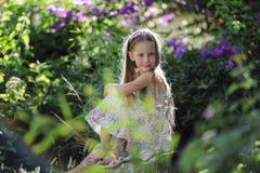 Flickan i parkerar bland blommor fotografering för bildbyråer