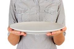 Flickan i plädskjortan rymmer en tom rund matte platta främst av henne tom maträtt för kvinnahandhåll för dig som desing Perspect royaltyfria bilder