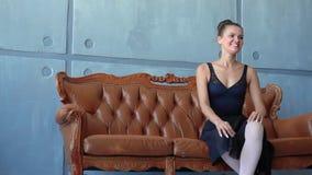Flickan i pointes sitter på en soffa på balettskolan Den härliga ballerina poserar för ett foto i studion av baletten lager videofilmer