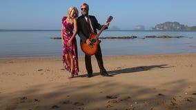 Flickan i röda omfamningar till gitarrister går mot på stranden på gryning stock video