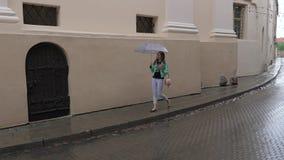 Flickan i regnigt väder går under ett paraply på en smal gata av staden stock video
