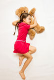 Flickan i rosa färger klär att sova på stor nallebjörn på golv Arkivfoto