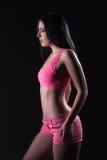 Flickan i rosa färger på en svart bakgrund Arkivfoto