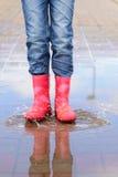 Flickan i rosa färger startar banhoppning i pölar Arkivbilder