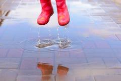 Flickan i rosa färger startar banhoppning i pölar Royaltyfri Bild
