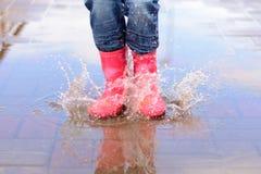 Flickan i rosa färger startar banhoppning i pölar Arkivbild