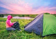 Flickan i rosa färgomslag öppnar hennes ryggsäck nära tältet på flodlodisarna fotografering för bildbyråer