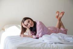 Flickan i rosa pyjamas som ligger på sängen och, lyssnar till musik med hörlurar royaltyfri foto