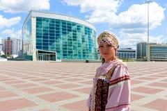 Flickan i ryssfolkdräkt står på fyrkanten Arkivfoto