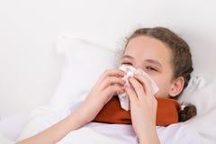 Flickan i säng blåser ett snor från hennes näsa in i en servett Royaltyfri Foto