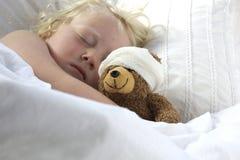 Flickan i säng som kelar en nalle med, förbinder Royaltyfri Bild