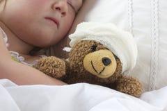 Flickan i säng som kelar en nalle med, förbinder Arkivbilder