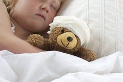 Flickan i säng som kelar en nalle med, förbinder Arkivfoto