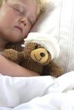 Flickan i säng som kelar en nalle med, förbinder Fotografering för Bildbyråer