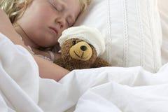 Flickan i sängkelnalle med förbinder Royaltyfria Foton