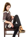 Flickan i sandals är sammanträde på en gammal träfåtölj Royaltyfri Foto