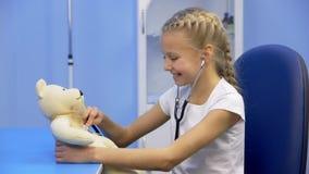Flickan i sjukhuset spelar med en nallebjörn arkivfilmer