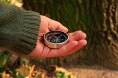 Flickan i skog rymmer en kompass i hennes hand Fotografering för Bildbyråer