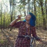 Flickan i skogen, på en cykel, dricker vatten från en flaska royaltyfria foton