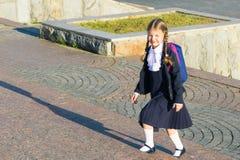 Flickan i skolalikformig med en ryggsäck stiger en stege royaltyfri fotografi