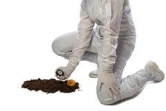 Flickan i skyddande dräkt gör jordmätningar som isoleras på vit arkivfoton