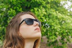 Flickan i solglasögon regnar se himlen fotografering för bildbyråer