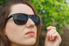 Flickan i solglasögon regnar se himlen arkivfoto