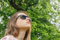 Flickan i solglasögon regnar se himlen Arkivbilder