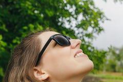 Flickan i solglasögon regnar se himlen Royaltyfri Foto