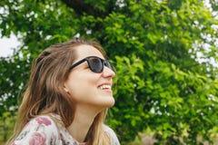 Flickan i solglasögon regnar se himlen Royaltyfri Fotografi