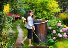 Flickan i sommaren grinar blom- blomningträdgårdintelligens arkivbilder