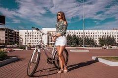 Flickan i sommaren i stad, står bredvid en vit cykel, i en vit kjol och en grön blus Ljus solig dag in arkivfoton
