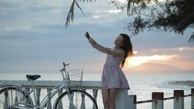 Flickan i sommarklänning gör selfie på invallningen nära en strand på solnedgången stock video