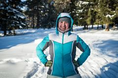 Flickan i spela för vinterskog kastar snöboll royaltyfri fotografi