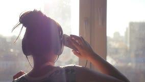 Flickan i stor hörlurar som dansar nära ett fönster på en stadsbakgrund, sol rays med en telefon i händer Slowmo 1920x1080 arkivfilmer