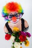 Flickan i stor svart exponeringsglas och clowndräkt med en bukett av blommor ser upp arkivfoton