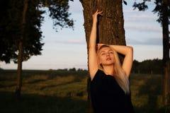 Flickan i strålar av aftonsolnedgångsolen Arkivbild