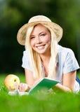 Flickan i sugrörhatt med äpplet läser boken på gräset royaltyfri foto