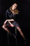 Flickan i svart på en stol Royaltyfri Bild