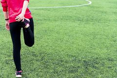 Flickan i svart sportdamasker och ett rosa omslag knådar, innan han utbildar i en öppen sportarena royaltyfri fotografi
