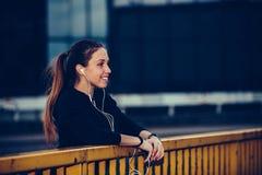 Flickan i svarta sportar utrustar att vila, når han har kört på bron, på natten fotografering för bildbyråer
