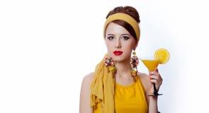 Flickan i 70-talkläder utformar med den tropiska coctailen Arkivfoton