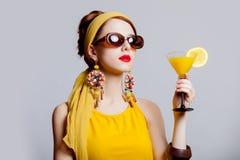 Flickan i 70-talkläder utformar med den tropiska coctailen Royaltyfri Foto