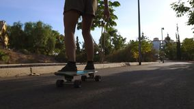 Flickan i ultrarapid rider en skateboard i parkerar med palmträd lager videofilmer