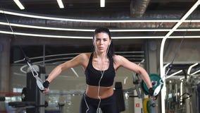 Flickan i utarbetande och utbildande skuldror för sportswear med övning bearbetar med maskin övergång i idrottshall stock video