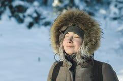 Flickan i varmt vinteromslag med en huv med päls, ögon stängde sig och att le som tycker om det härliga vädret royaltyfria foton
