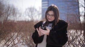 Flickan i vinter i en snöig stad skriver ett meddelande till hans vänner på smartphonen lager videofilmer