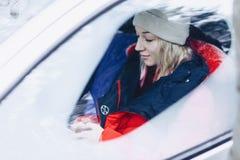 Flickan i vinterkläderna i bilen ser telefonen royaltyfria bilder