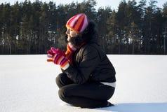 Flickan i vintern som håller ögonen på solnedgången Fotografering för Bildbyråer